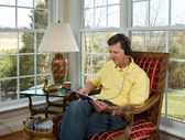 Boomer reading on tablet computer — Stock Photo