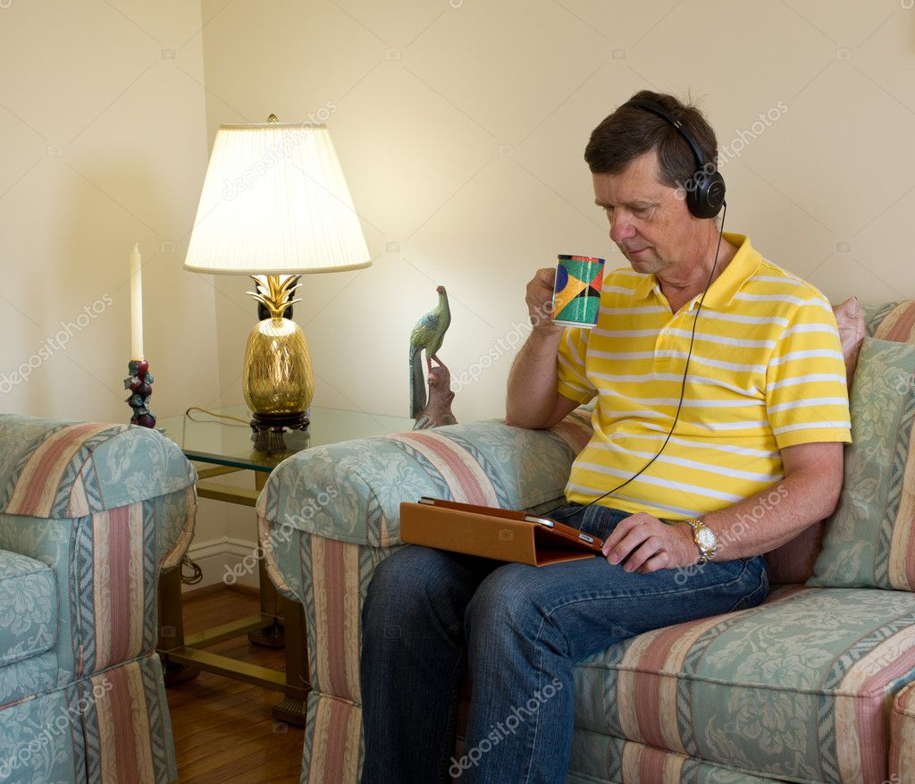 Senior male sitting in modern room and watching from a tablet computer with headphones on his head — Stock Photo #5221790
