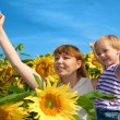 Happy mother and daughter in a field of sunflowers — Stock Photo #4099413