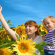 Stock Photo: Happy mother and daughter in a field of sunflowers