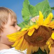 Stock Photo: Beautiful little girl and sunflowers