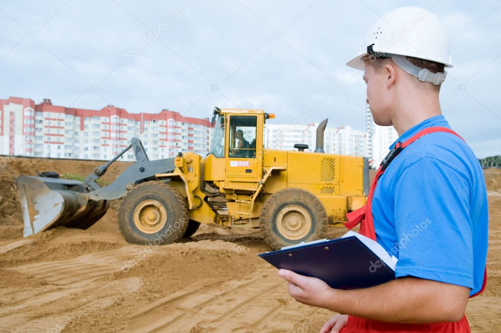 One builder worker with clipboard inspecting earthmoving works at construction site. Focus on worker  Stock Photo #5366024