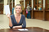 Young woman holding a paper in hand — Stock Photo