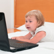 Royalty-Free Stock Photo: A small child is sitting with a laptop on the bed