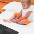 A small girl is sitting with a laptop on the bed — Foto de Stock
