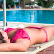 A beautiful young girl in a bikini sunbathing on a lounger — Stock Photo