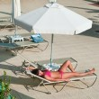 Beautiful young woman sunbathing on a lounger near the hotel — Stock Photo