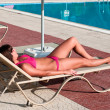Beautiful young woman in bikini sunbathing on a lounger — Stock Photo