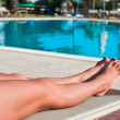 Legs of beautiful young unrecognizable woman in a bikini lying near pool — Stock Photo #4251403