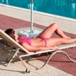 A beautiful young girl in a bikini sunbathing on a lounger near pool — Stock Photo