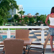Young beautiful girl standing on the balcony of the hotel — Stock Photo