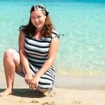 Young pretty girl on a sandy beach near the shore blue sea — Stock Photo #4259477