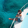 Stock Photo: Woman sitting on edge of yacht
