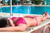 Krásná mladá dívka v plavkách opalovat na lehátku — Stock fotografie