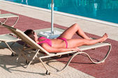 A beautiful young girl in a bikini sunbathing on a lounger near pool — Стоковое фото