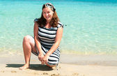 Young pretty girl on a sandy beach near the shore blue sea — Stock Photo