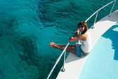 Woman sitting on edge of yacht — Stock Photo