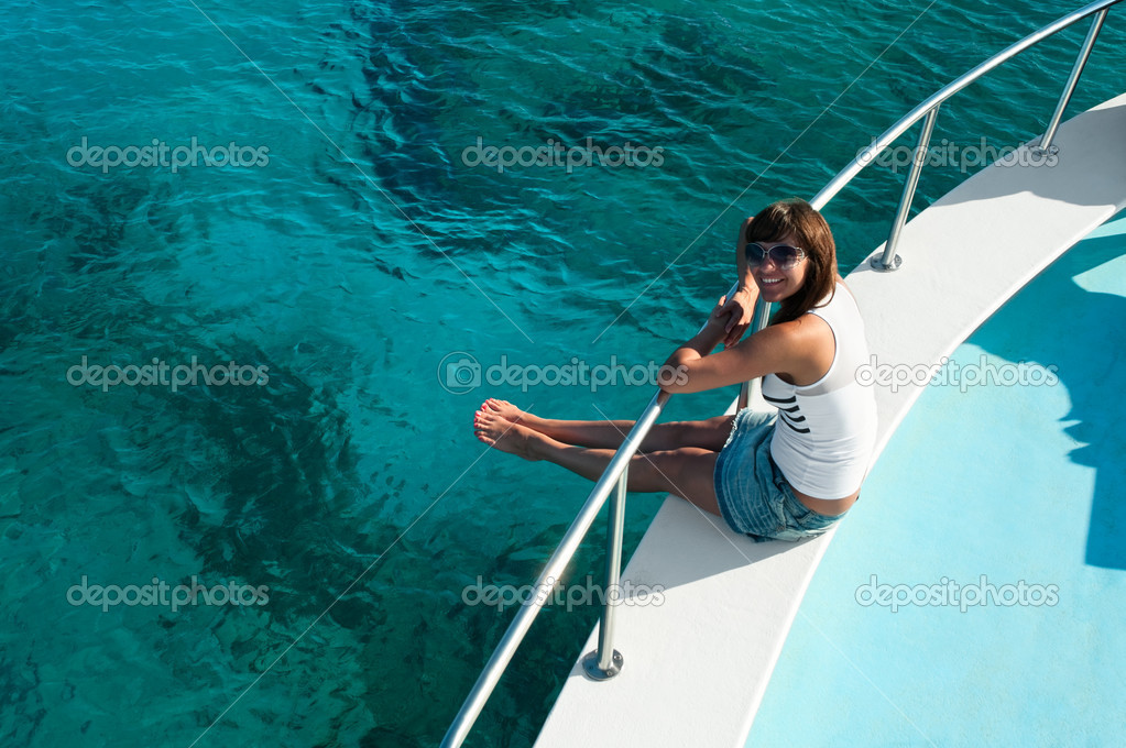Young beautiful girl sitting on a yacht with his legs hanging in the blue sea — Stock Photo #4259481