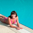 Beautiful young girl in a bikini lying near a pool of blue water — Stock Photo #4267265