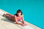 Beautiful young girl in a bikini lying near a pool of blue water — Stock Photo