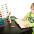 The little girl sits at a table and does a homework — Stock Photo #4515763