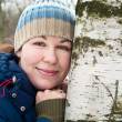 Pretty young woman lean against a birch. — Stock Photo #4515790