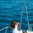 Women on yacht in blue sea seating on stern. — Stock Photo