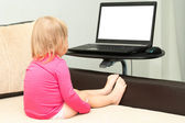 Little child is sitting with a laptop on the bed. — Stock Photo
