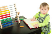 The little girl sits at a table and does a homework — Stock Photo
