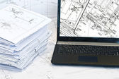 Laptop and stack of project drawings. — Stock Photo