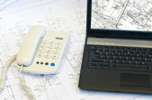 Laptop, phone on project drawings — Stock Photo