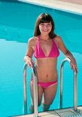 Belle jeune fille en bikini s'éteint de la piscine avec l'eau bleue — Photo