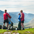 Group of travelers in mountains with knapsacks — Stock Photo