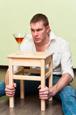Drunken man sitting on floor with glass of alcohol — Stock Photo