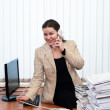 Young caucasian woman in office interior calling by telephone and stack of  — Stok fotoğraf