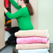 Stack of clothes and young caucasian woman arranging things in the wardrobe — Stock Photo #5169067