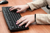 Female hands typing on a black keyboard — Stock Photo