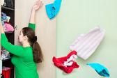 Młody kaukaski kobieta rzucając ubrania — Zdjęcie stockowe