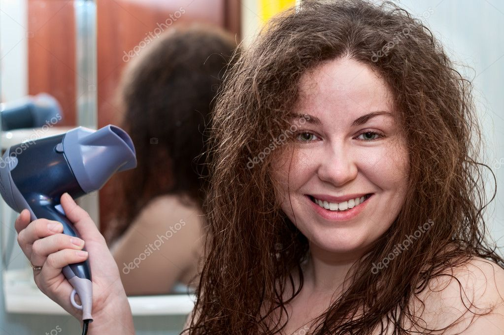 Young caucasian woman with curly brown bushy hair holding hairdryer — Stock Photo #5169004