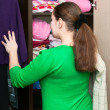 Foto Stock: Young woman thinking about to put on near wardrobe