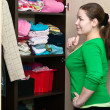Young woman thinking about to put on near wardrobe - Foto Stock