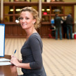 Stock Photo: Young beautiful blond girl sitting at a table near the bar with the informa