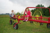 Children sitting on Yellow and red haymaker — Stock Photo