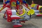 Girl playing in airplane carousel — Stock Photo