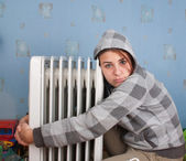 Young girl is sitting near heater — Stock Photo