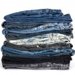 Stack of various jeans isolated on white — Stock Photo