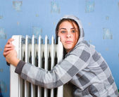 The freezing girl about a heater — Stockfoto