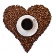 Stock Photo: White cup of coffee on heart shaped coffee beans