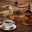Sack of coffee beans, white cup and coffee-grinder still life — Stock Photo
