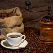 Sack of coffee beans, white cup and coffee-grinder still life — Stock Photo #5039311